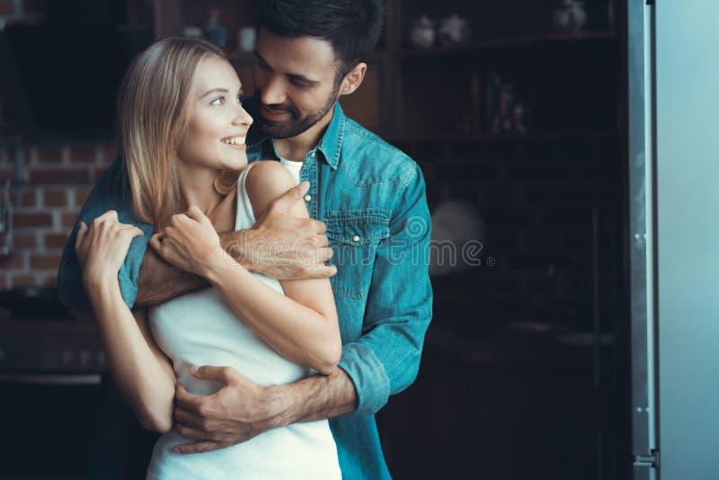 Unga lyckliga par som kramar och ser de i inre av ett nytt kök, lycka i ett nytt hem royaltyfri bild