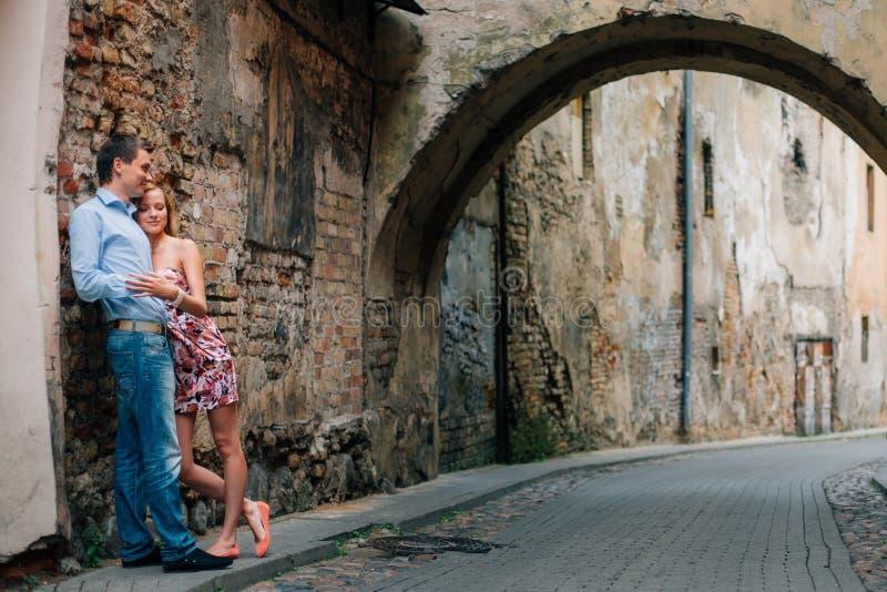 Unga lyckliga par som kramar på gatan royaltyfri foto