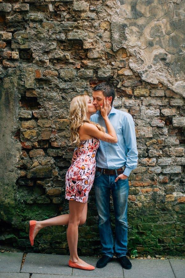 Unga lyckliga par som kysser på gatan royaltyfri foto