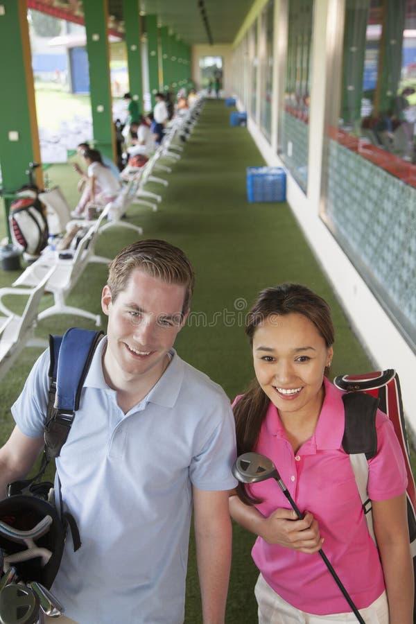 Unga lyckliga par som lämnar golfbanan med golfklubbar och teburken arkivfoto
