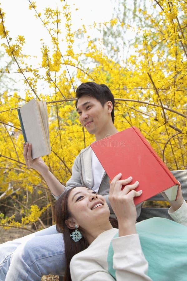 Unga lyckliga par som ligger och sitter på en parkerabänk som tycker om läsa deras böcker, utomhus i vår royaltyfri fotografi