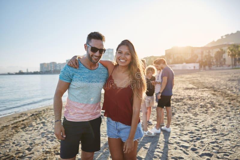 Unga lyckliga par som omfamnar sig på stranden royaltyfri foto