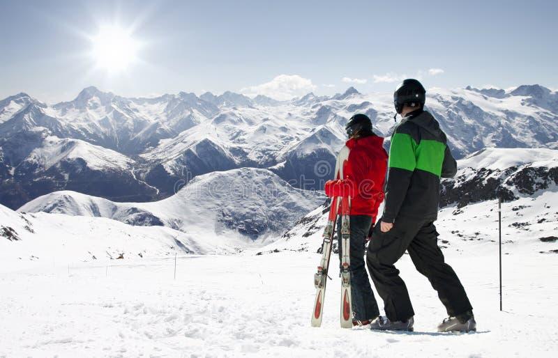 Unga lyckliga par som ser i snöig berg arkivbilder