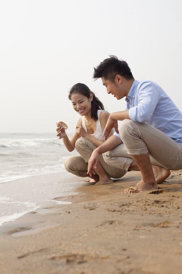 Unga lyckliga par som ser snäckskalet på vattnet, kantar, Kina royaltyfri fotografi
