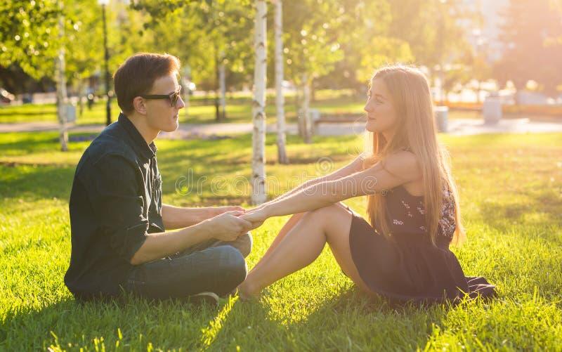 Unga lyckliga par som tillsammans talar utomhus- - sammanträde på gräs royaltyfri foto