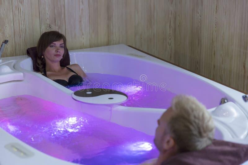 Unga lyckliga par som tycker om badet i brunnsortmitt royaltyfria foton