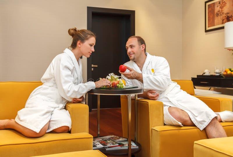 Unga lyckliga precis gifta Caucasian par i vita badrockar som har frukter efter brunnsort på bröllopsresa Mannen erbjuder ett äpp royaltyfria bilder
