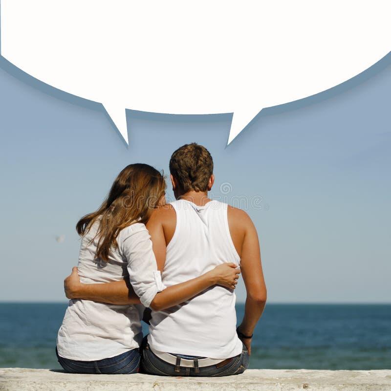 Unga lyckliga romantiska par på havskusten med dialogasken ovanför dem arkivfoton