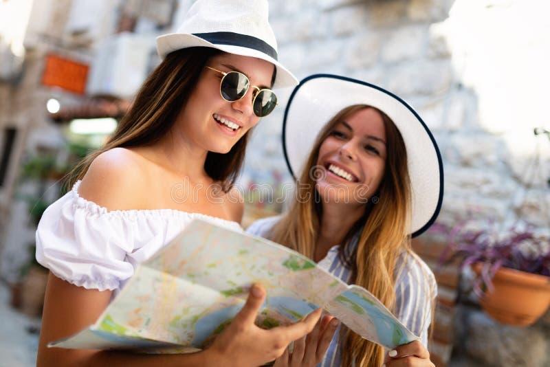 Unga lyckliga turist- kvinnor som reser på sommarsemester Lopp vänner, sommarbegrepp fotografering för bildbyråer