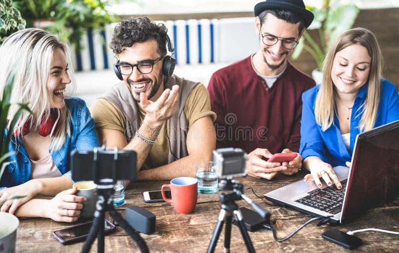 Unga lyckliga vänner som delar innehållet på tryckning av plattformen med den digitala rengöringsdukkameran - modernt marknadsför royaltyfria foton