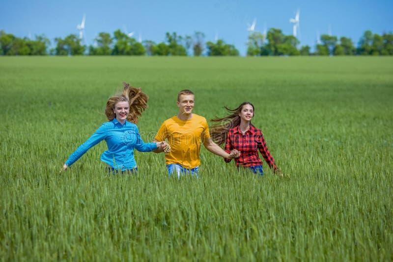 Unga lyckliga vänner som kör på grönt vetefält royaltyfri foto