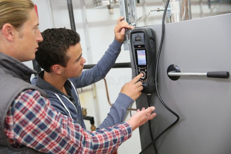 Unga män i yrkesutbildning som kontrollerar värmepumpen royaltyfri bild