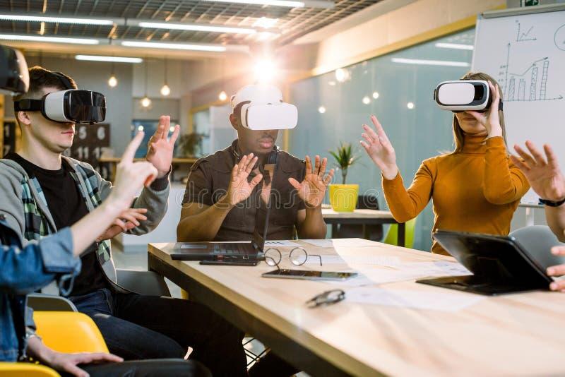 Unga män och kvinnor som sitter på en tabell med virtuell verklighetskyddsglasögon Multiethnical affärslag som testar virtuell ve arkivfoton