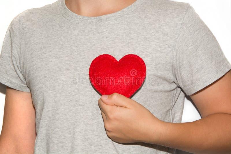 Unga män rymmer röd hjärta i hand royaltyfri foto