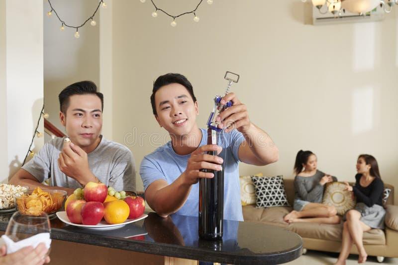 Unga män som öppnar vinflaskan arkivbild