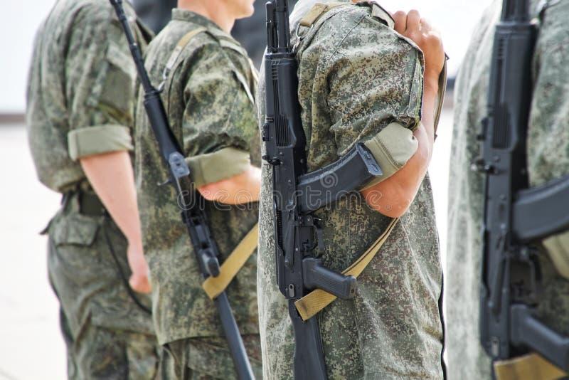 Unga män som beväpnas med automatiska vapen, i skyddande kaki- kläder på gatorna av staden Patrull eller säkerhet arkivfoto