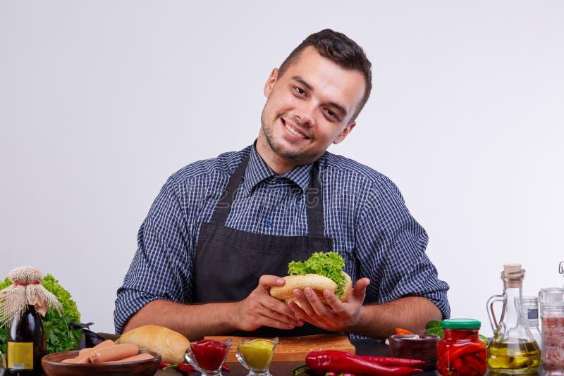 Unga män som gör hotdogen i köket Ingredienser för varmkorv fotografering för bildbyråer