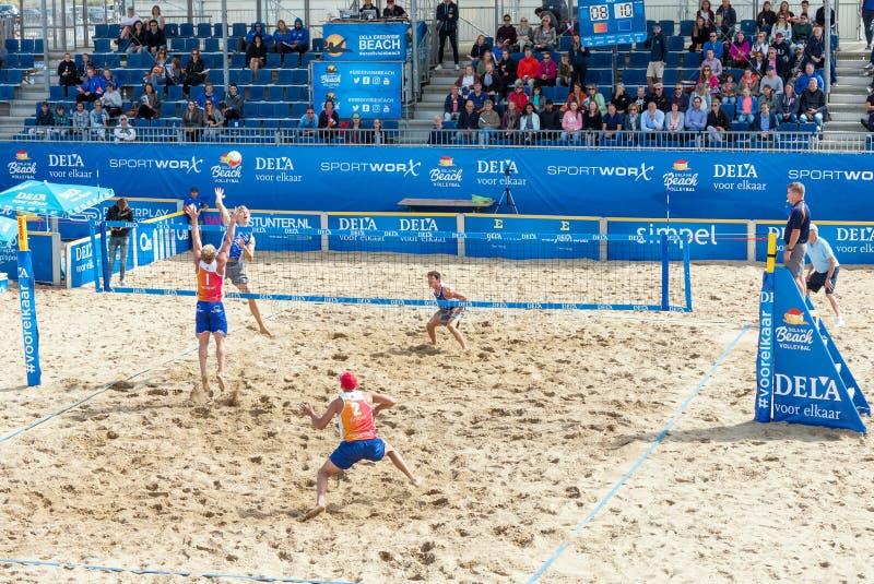 Unga män som spelar den yrkesmässiga matchen för strandvolleyboll i utomhus- arena royaltyfria bilder