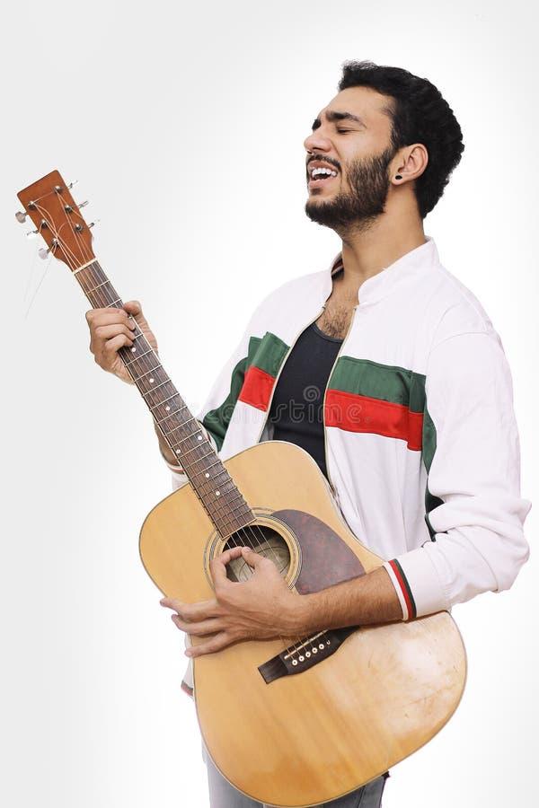 Unga män som spelar gitarren och den sjungande sången som isoleras på vit royaltyfri fotografi