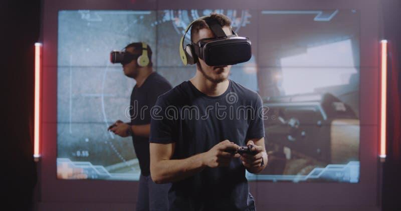 Unga män som spelar VR-leken royaltyfri fotografi