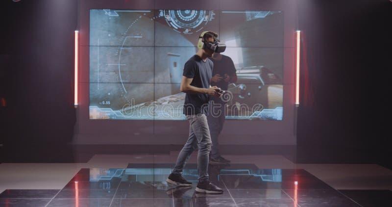 Unga män som spelar VR-leken arkivfoto