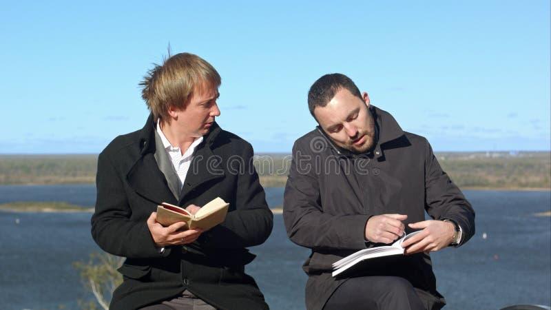 Unga män som talar på telefonen och, störer affärsmannen med booj arkivfoto