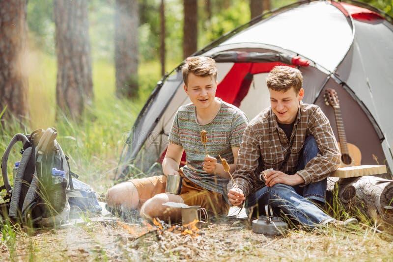 Unga män värmas i en brand och en kock ut på en sommarskog fotografering för bildbyråer