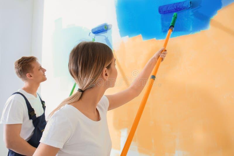 Unga målare som använder rullar för renovering av färg av väggen inomhus royaltyfria foton