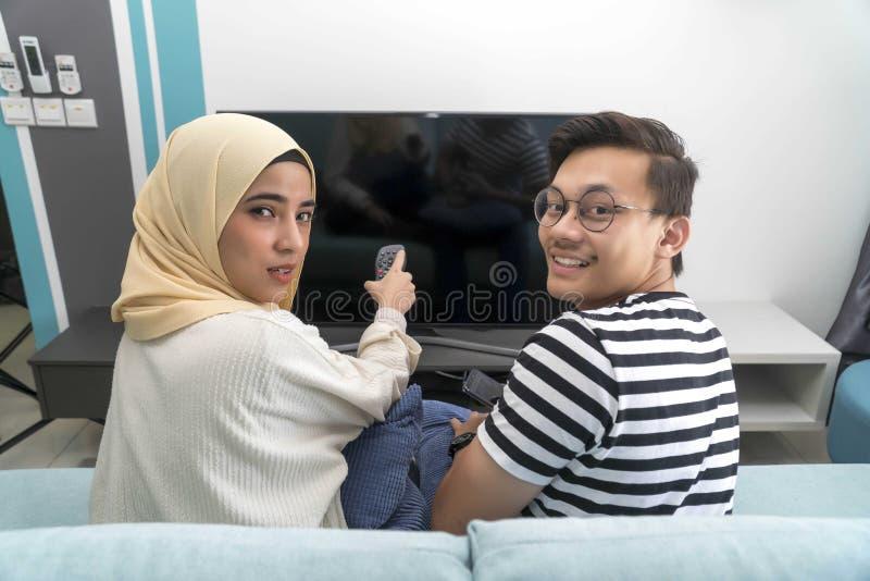Unga malajiska par p? den h?llande ?gonen p? tv:n f?r soffa tillsammans royaltyfri fotografi