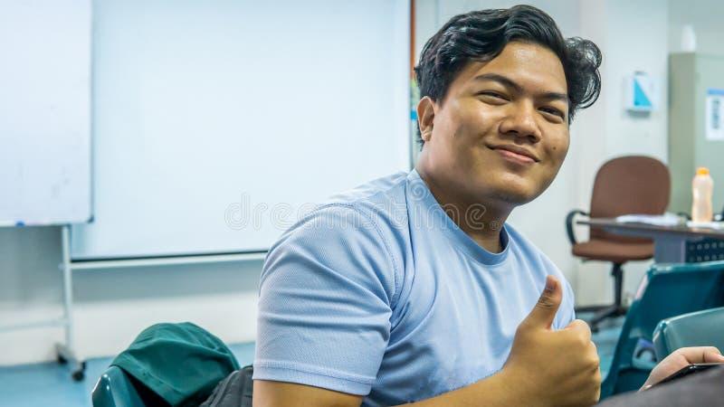 Unga Malay-studenten leker med ljusa ögon och visar tummen upp eller gott tecken i klassrummet royaltyfria bilder