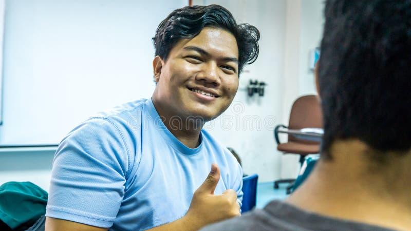 Unga Malay-studenten leker med ljusa ögon och visar tummen upp eller gott tecken i klassrummet fotografering för bildbyråer