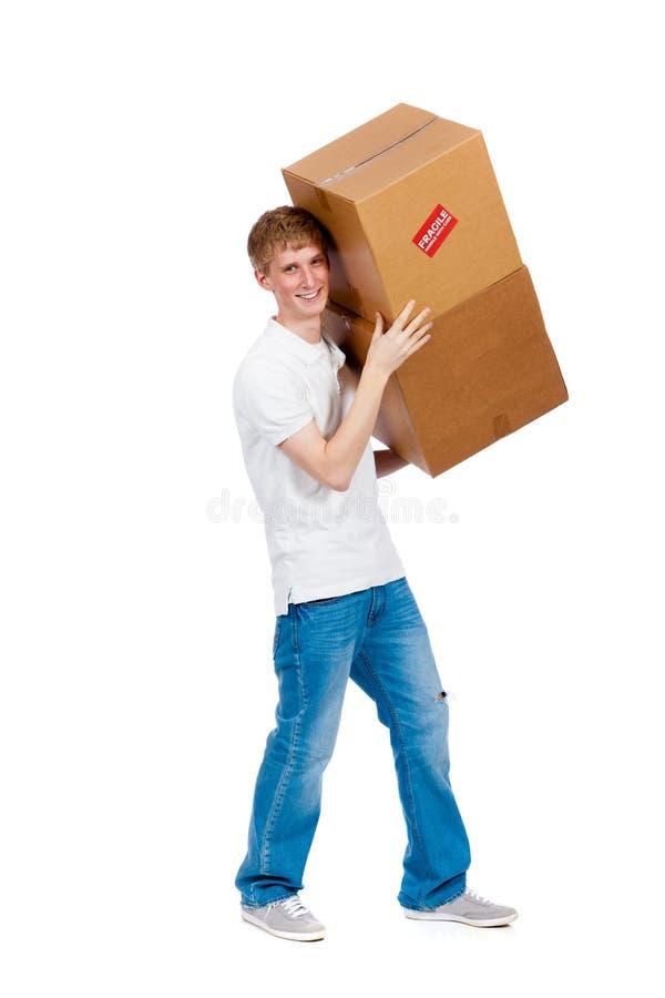Unga manliga bärande flyttande askar fotografering för bildbyråer