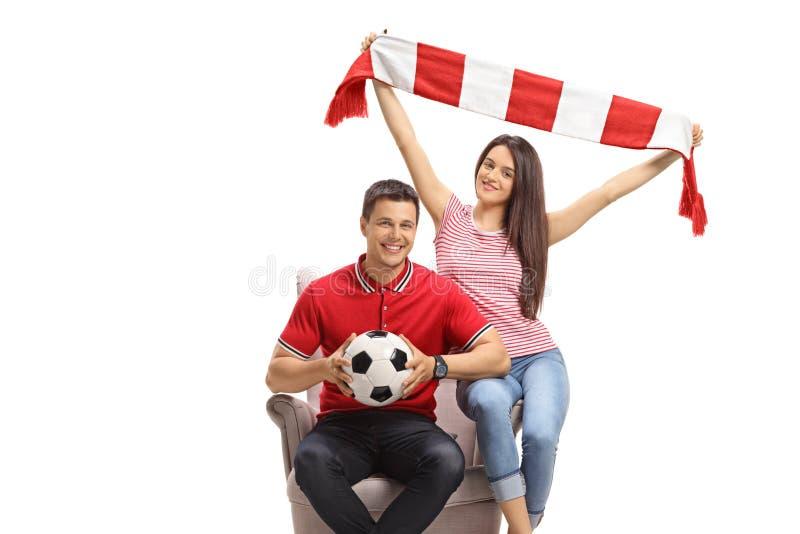 Unga manliga och kvinnliga fotbollssupportrar med fotboll och en scarf som sitter i en stol royaltyfria bilder