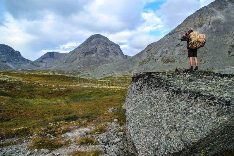 Unga manliga turist- fotografier härliga berg med mossa royaltyfri foto