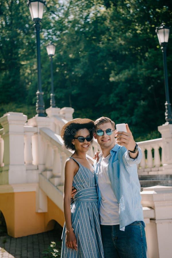 unga mellan skilda raser par i solglasögon som tar selfie på smartphonen arkivbild