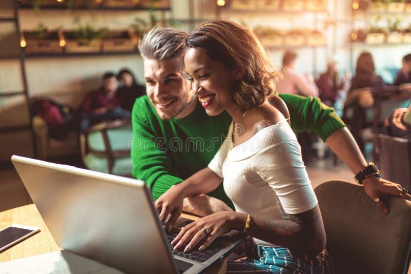 Unga mellan skilda raser par som spenderar tid i hållande ögonen på massmedia för kafé arkivfoto