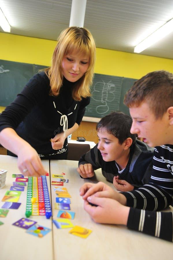 Unga migranter i den tyska skolan som tillsammans spelar royaltyfria bilder
