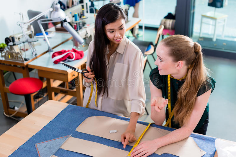 Unga modeformgivare som talar om orientering royaltyfria foton