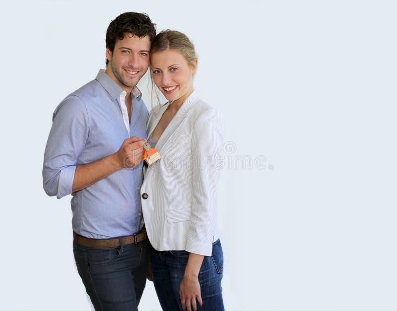 Unga moderiktiga par med tangenter av det nya huset arkivbild