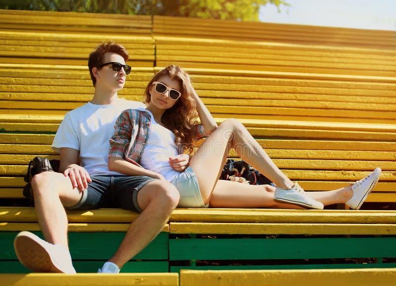 Unga moderna stilfulla hipsters som par vilar i bänkstad, parkerar fotografering för bildbyråer