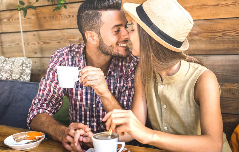 Unga modevänpar på början av kärlekshistorien - den stiliga mannen som kysser den härliga kvinnan på coffee shopstången - förhåll arkivbild