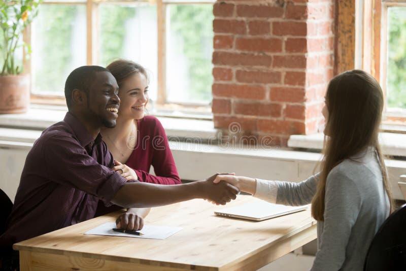 Unga multietniska par som skakar händer med fastighetsmäklaren royaltyfri foto