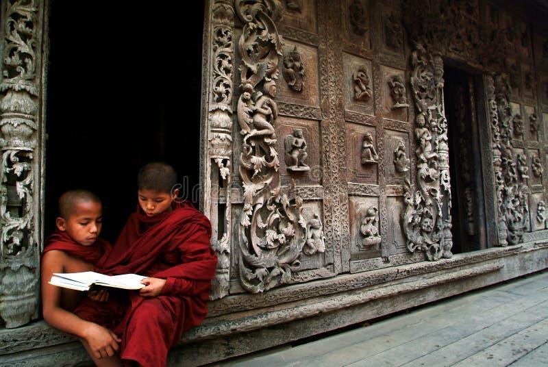 Unga munkar som läser en bok på den Shwenandaw kloster royaltyfri foto