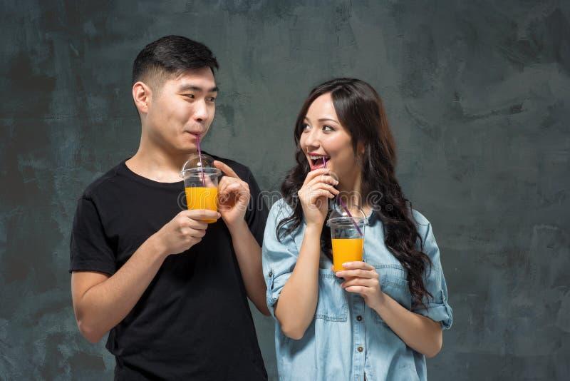 Unga nätta asiatiska par med exponeringsglas av orange fruktsaft royaltyfria bilder