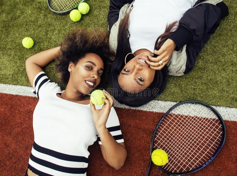 Unga nätta flickvänner som hänger på tennisbanan, danar det stilfulla klädda byltet, lyckligt le för bästa vän tillsammans arkivbild