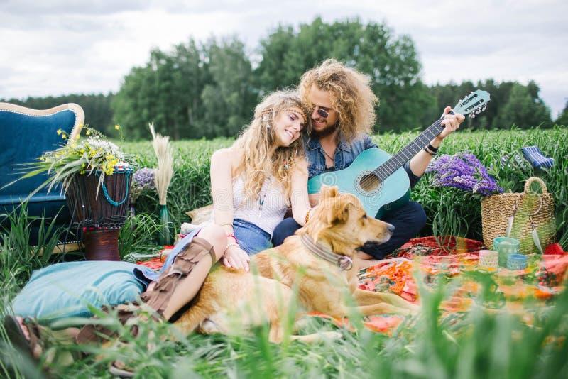 Unga nätta hippiepar med den utomhus- gitarren och hunden fotografering för bildbyråer
