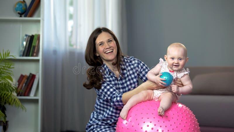 Unga nätta moderlekar med behandla som ett barn flickan, tidiga utvecklingsövningar för spädbarn arkivfoton