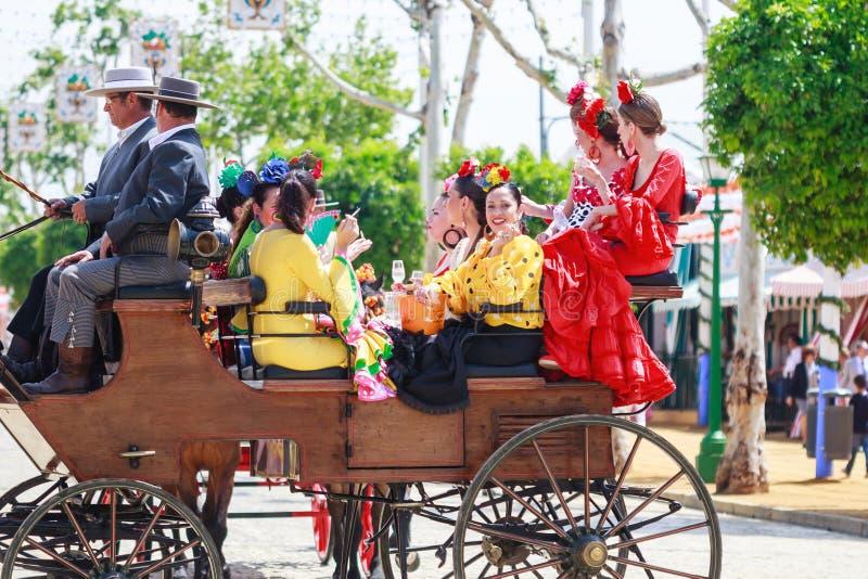Unga och härliga kvinnor på en häst dragen vagn under April Fair av Seville arkivfoto
