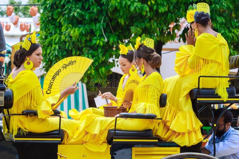Unga och härliga kvinnor på en häst dragen vagn under April Fair av Seville arkivbilder