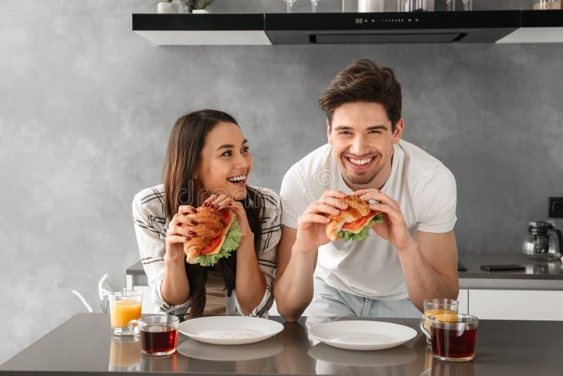 Unga och härliga par som ler och äter smörgåsar på bre royaltyfri foto